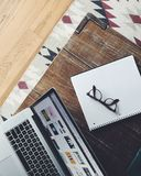 Black Frame Eyeglasses on Top of White and Black Spiral Notebook Beside Macbook Pro on Brown Wooden Table Royalty Free Stock Images