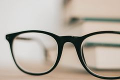 Black frame glasses in front of pile of books stock image