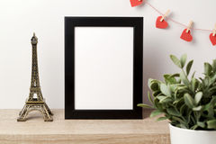 Black frame mock up. With Effiel tower, plant and heart shape garland. Modern stylish interior background for social media and marketing Stock Images