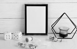 Black frame mockup with interior items. On white wooden background. Poster product design styled mock-up.Copy space Stock Image