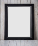 Black frame placed vertically on wooden background, mock up. A portrait of a Black frame placed vertically on wooden background, mock up Royalty Free Stock Photo