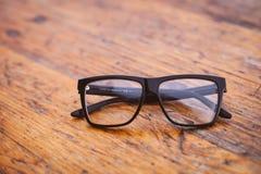Black Frame Wayfarer Eyeglasses on Brown Wooden Surface stock photo