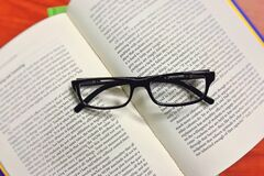 Black Framed Eyeglasses on Book Stock Images