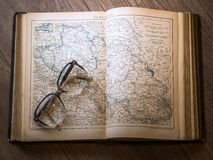 Black Framed Eyeglasses Map in Book Stock Photos