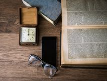 Black Framed Eyeglasses on Top of Black Smartphone Near Brown Square Analog Clock on Brown Wooden Surface Stock Images