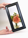 Black Framed Floral. A peachy rose artificial floral arrangement behind a black frame being held up by a hand. Over a white background Royalty Free Stock Photos