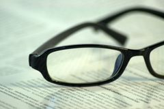 Black-framed glasses lie on the page of the magazine. stock image