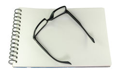 Black framed glasses lying open on a sketch book. Pair of black framed glasses lying open on a spiral bound blank white sketch book, high angle view isolated on Royalty Free Stock Image