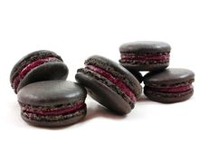 Black French macarons with dark red fruit filling isolated on white background stock photo