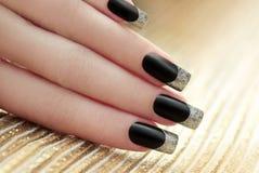 Black French manicure. Black French manicure on Golden striped background stock photo