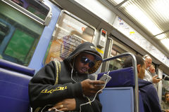 Black Frenchman looks into Apple iphone on Metro Train, Paris, France - shot August 2015 Royalty Free Stock Photography