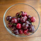 black fresh freshly picked cherries in bowl on wooden table.. Stock Image