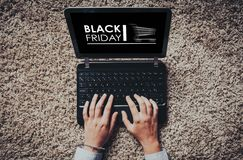 Black Friday advertisement in a laptop screen while woman uses it to shopping by internet. Royalty Free Stock Photo