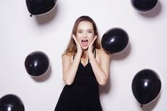 Black friday, a beautiful girl in a black dress with long hair smiles and looks at the camera. Black balloons are flying, the girl