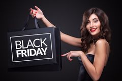 Sale. Young smiling woman showing shopping bag in black friday holiday. Black Friday. Beautiful smiling woman showing shopping bag make her thumb up in black royalty free stock photo