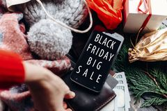 Black friday big sale. hand on wallet. special christmas offer d. Iscount text on mobile phone screen message on seasonal rustic background with money  and bag Stock Photo