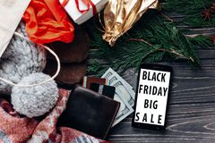 Black friday big sale. special christmas offer discount text on. Mobile phone screen message on seasonal rustic background with money cards wallet and bag with Stock Image
