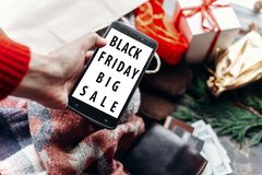Black friday big sale special offer. woman holding phone with di. Scount text on screen message on seasonal rustic background with money and bag with presents Royalty Free Stock Photography