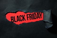 Black friday. Black torn paper and the inscription `black friday` on a red background Royalty Free Stock Images