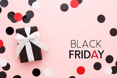 Black friday card with gift box and confetti on pink background. Black friday card. Black gift box with white bow and confetti on pink background. Top view royalty free stock photography
