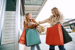 Black friday concept. Happy friends shopping. Two beautiful young women enjoying shopping in the city Royalty Free Stock Images