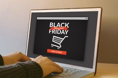 Black friday concept on laptop computer screen on wooden table. Hands typing on a keyboard. All screen content is designed by me Royalty Free Stock Photography