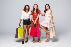 Black friday concept. Portrait of cheerful three mixed race women holding colorful bags in raised hands enjoying seasonal sales stock image