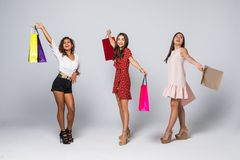 Black friday concept. Portrait of cheerful three mixed race women holding colorful bags in raised hands enjoying seasonal sales stock images