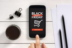Black Friday concept on smart phone screen with office objects. On white wooden table. All screen content is designed by me. Flat lay Royalty Free Stock Photos