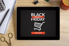 Black friday concept on tablet screen with office objects. On wooden desk. All screen content is designed by me. Top view Royalty Free Stock Images