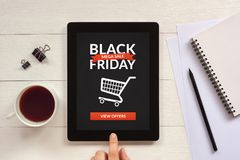 Black Friday concept on tablet screen with office objects. On white wooden table. All screen content is designed by me. Flat lay Stock Images