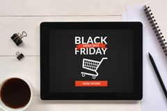 Black Friday concept on tablet screen with office objects. On white wooden table. All screen content is designed by me. Flat lay Royalty Free Stock Photo