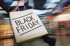 Black Friday craze. Crazy shopper moving in the mall with paperbag on Black Friday Stock Photography