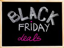 Black Friday deals advertisement handwritten with chalk on wooden frame blackboard Royalty Free Stock Photography