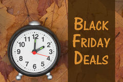 Black Friday deals message. Some fall leaves and retro alarm clock with text Black Friday Deals Royalty Free Stock Image