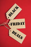 Black Friday Deals on sale tags - vertical. Black Friday Sale message sign on brown paper sale tags on red background. Vertical Stock Photography