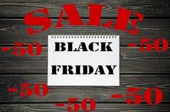 Black Friday försäljningar som annonserar affischen på svart träbakgrund Fotografering för Bildbyråer