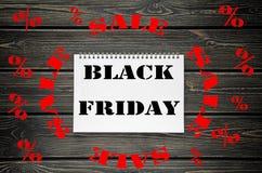 Black Friday försäljningar som annonserar affischen på svart träbakgrund Arkivfoto