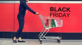 Black Friday-, Frauenkäufer und Einkaufstasche in einer Laufkatze stockbild