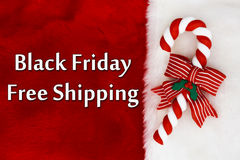 Black Friday Free Shipping. Red Plush background and a Candy Cane with text Royalty Free Stock Photography