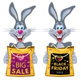 Black Friday. Funny rabbit holds shopping bag from the sale. Royalty Free Stock Image