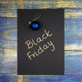 Black Friday geschrieben auf schwarze Karte mit Weihnachtsflitter Stockfotos