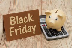 Black Friday, A golden piggy bank, card and calculator on wood b Stock Photography