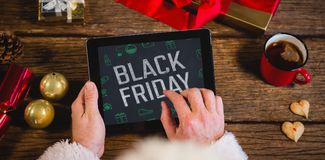 Composite image of black friday with green christmas icons. Black Friday with green Christmas icons against santa claus using digital tablet Stock Photography