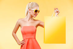 Black friday. Happy young woman shopping in holiday. Girl showing on bag with copy space Stock Photos