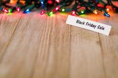 Black Friday-Listenkonzept auf hölzernem Brett und farbigen Lichtern, selektiver Fokus, Raum für Kopie Stockbilder