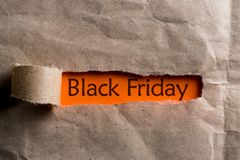 Black friday - message appearing behind ripped brown paper. Shopping time. Day with biggest Sale. Mockup.  Royalty Free Stock Photos