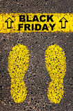 Black Friday message. Conceptual image. Black Friday message. Retail Sales Conceptual image with yellow paint footsteps on the road in front of horizontal line Stock Photo