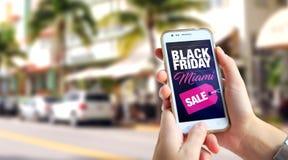Black Friday Miami Smartphone mit einer Black Friday-Werbung auf dem Schirm stockbilder