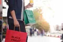 Black Friday, mulher com o copo de café que guarda sacos de compras imagens de stock royalty free